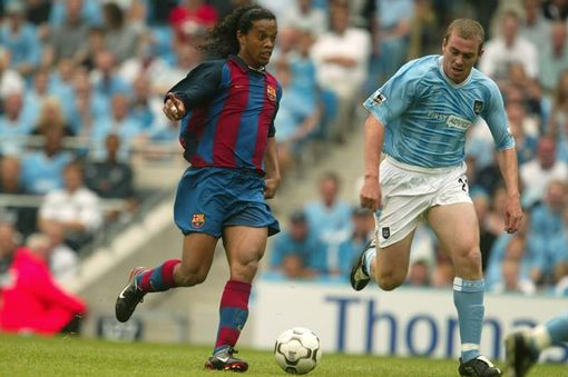 Ronandinho dances past Richard Dunne at the COMS curtain raiser